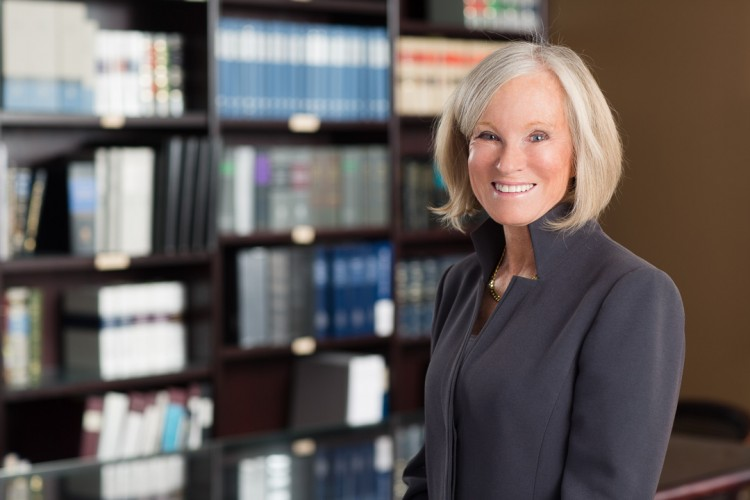 headshot of a female law partner with law books in the background