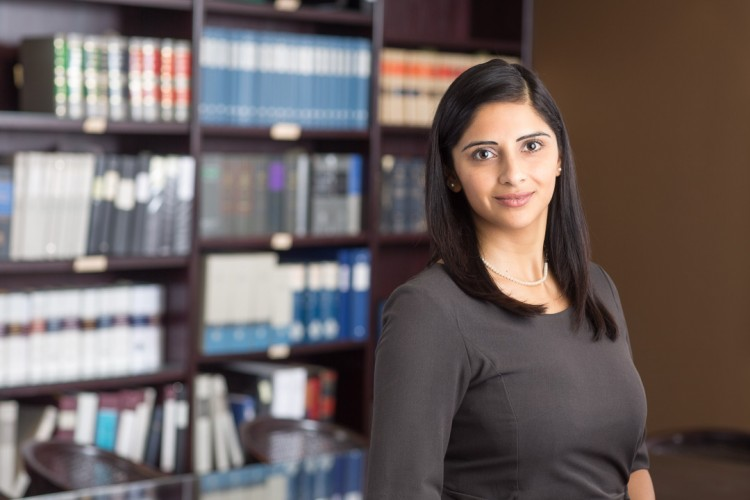 headshot of a female lawyer with law books in the background