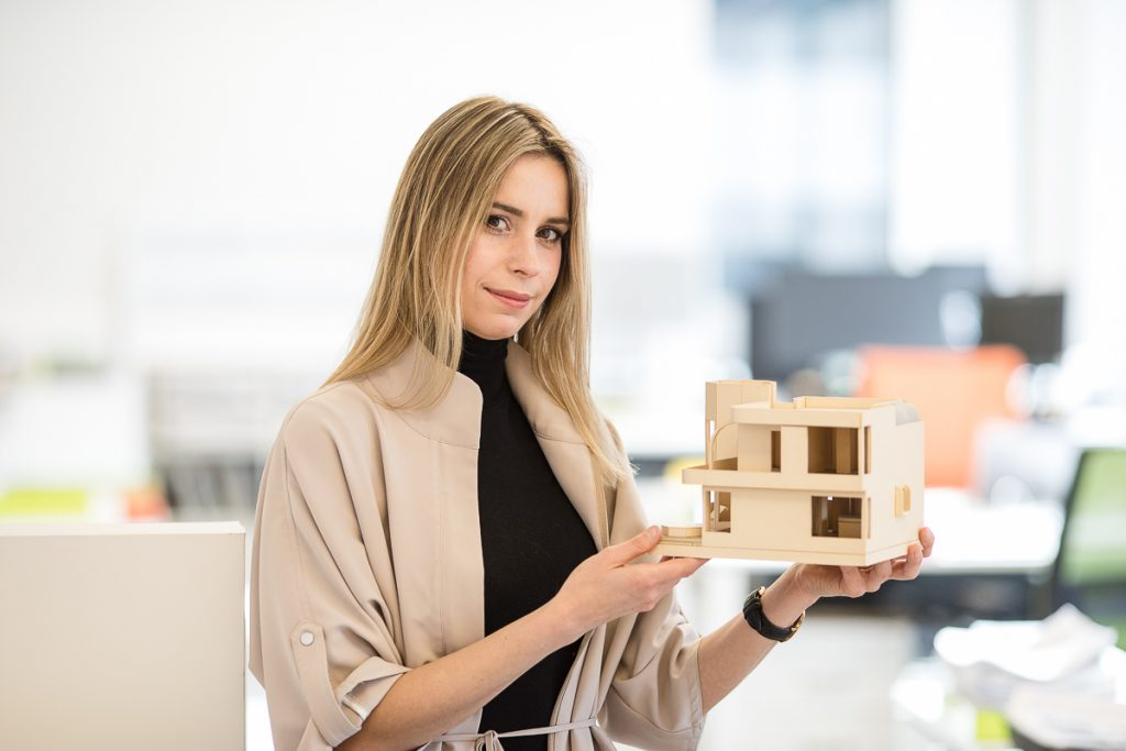 environmental staff portraits of an architect holding a model home